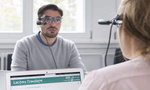 A user speaking into KIT's Lecture Translator, which shows translated words on screen.